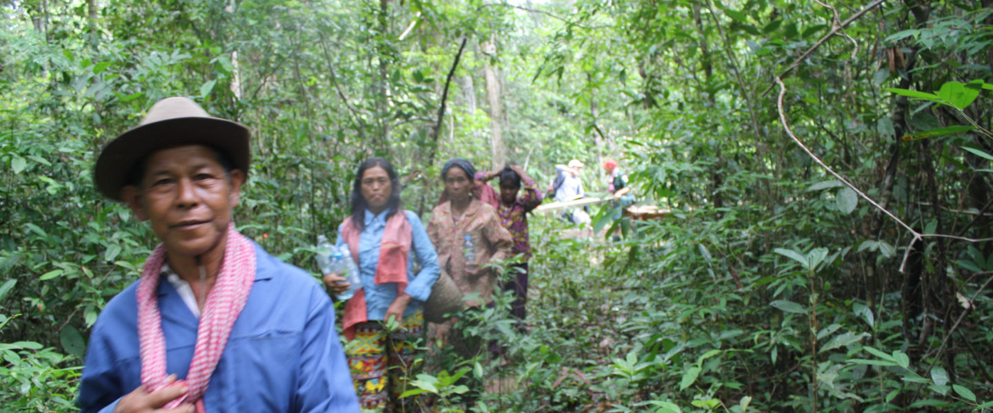Researchers and participant men and women walking through the forest